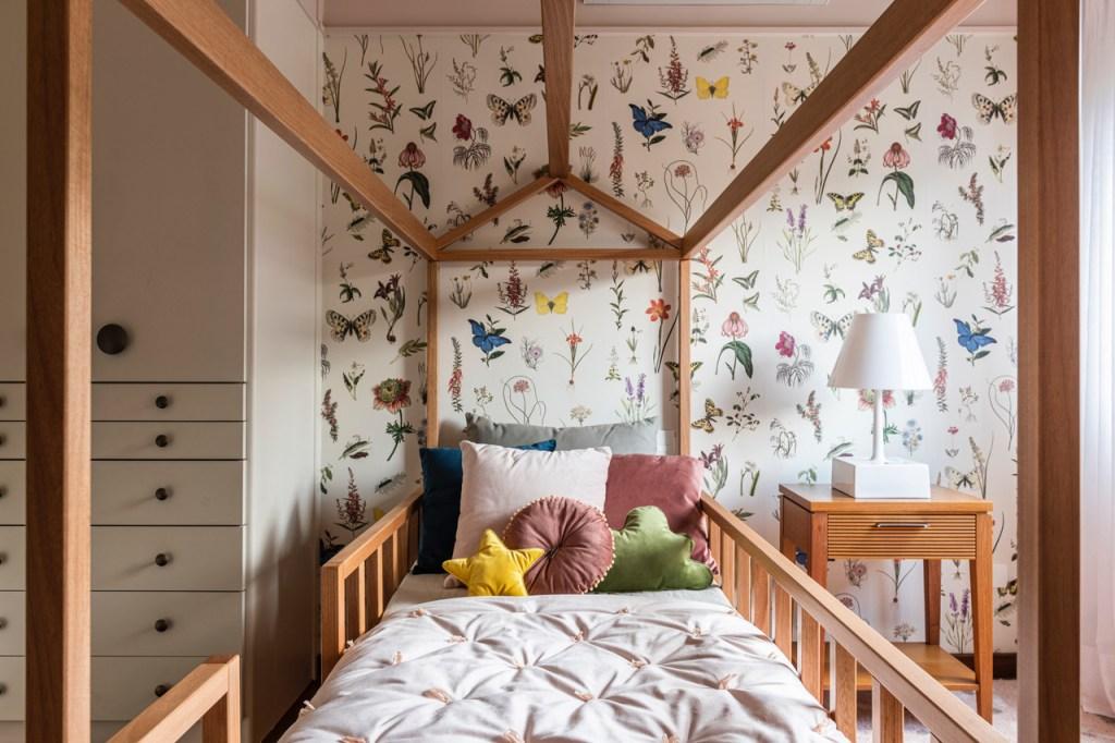 Quarto de criança com cama em madeira em formato de casinha. Travesseiros coloridos, um em formato de estrela, um redondo e um em formato de nuvem. Papel de parede com flores, borboletas e folhas em estilo botânico