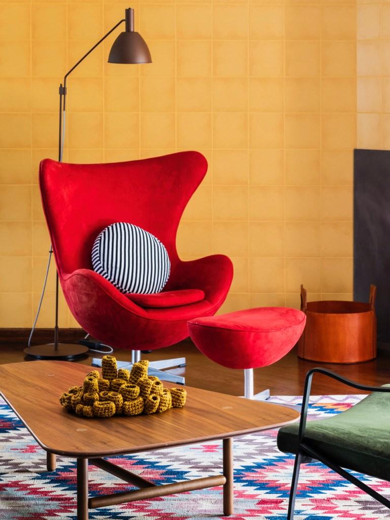 Poltrona Egg vermelha com encosto para os pés. Travesseiro redondo listrado branco e preto. Parede de azulejos amarelos ao fundo.