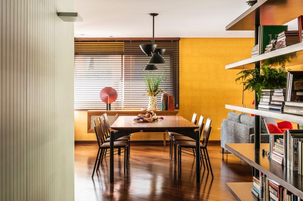Sala de estar. À direita, estante com livros e uma folhagem. Parede de madeira ripada branca à esquerda. Parede de azulejos amarelos ao fundo. Mesa de jantar com seis cadeiras em madeira