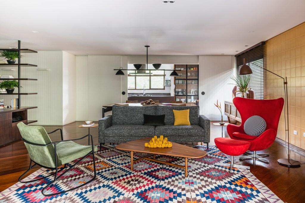 Sala de estar com piso em madeira escura. Sofá cinza, poltrona verde e poltrona egg vermelha. Tapete colorido com padrão quadriculado. Ao fundo, a porta de madeira ripada branca deslizante está aberta, revelando o balcão da cozinha
