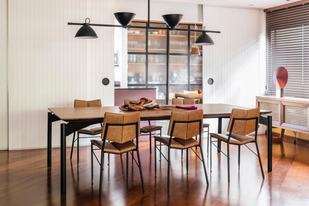 Estar com piso em madeira escura. Mesa de jantar em madeira com seis cadeiras com encosto em couro caramelo. Luminária preta. Porta de madeira branca ripada aberta, revelando estante de vidro da cozinha