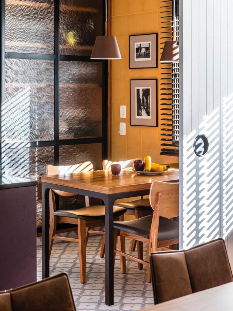 Porta de madeira branca ripada revelando cozinha. Armário com porta de vidro e detalhes pretos. Parede de azulejos amarelos da sala continua até a cozinha. Mesa de madeira com quatro lugares. Sol entrando pela persiana.
