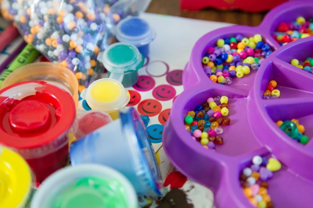 Imagem de mesa com miçangas, linhas, adesivos e miçangas coloridas