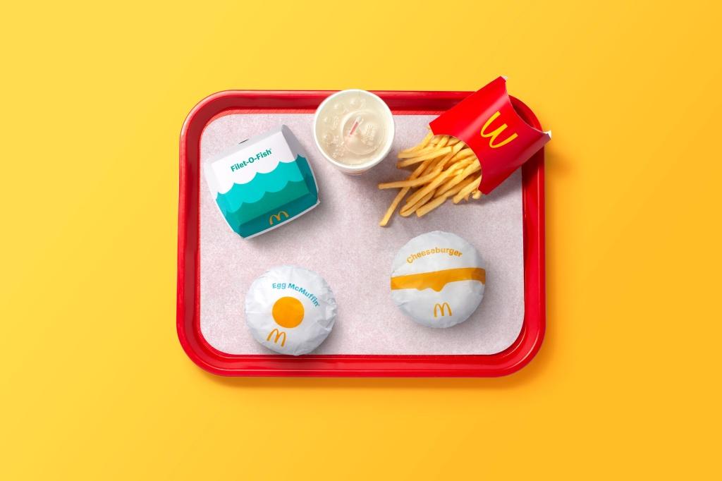 Bandeja vista de cima com cheeseegg, cheeseburguer, batata frita e caixa de mcfish com ondas azuis. Copo de refrigerante visto de cima