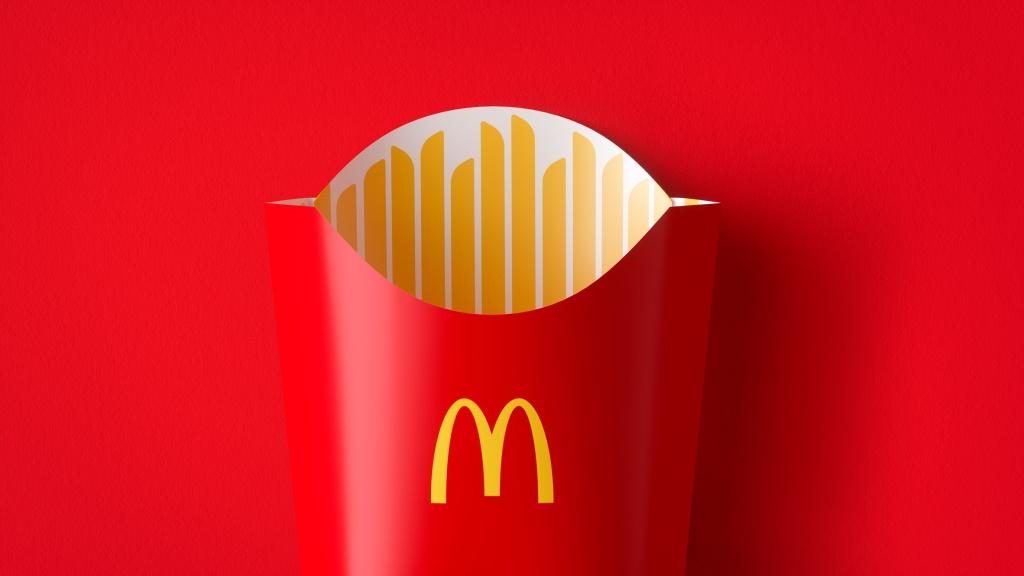 Embalagem de batata frita vermelha no fundo vermelho. Por dentro, retângulos amarelos representam as batatas.