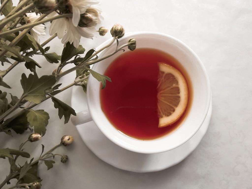 Xícara de chá branca com meia rodela de limão e chá. Flores ao lado