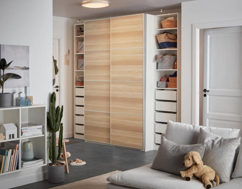 Quarto com armário com portas de madeira. Estante branca com livros à esquerda e sofá cinza à direita.