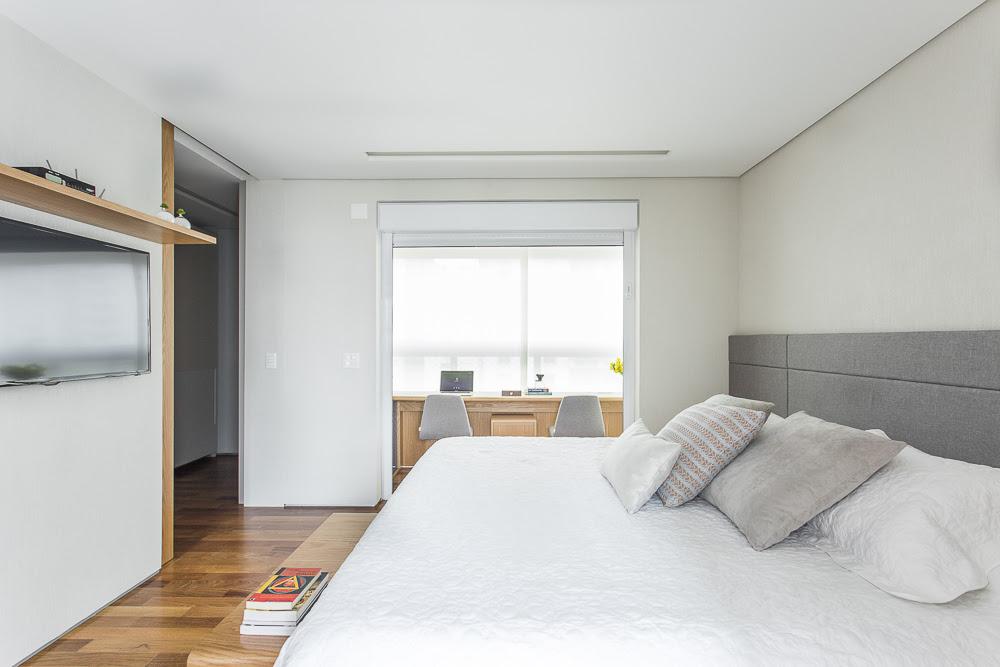 Quarto com paleta de cores claras e cama de casal. Ao fundo, varanda adaptada em home office. Bancada de madeira, computador e duas cadeiras