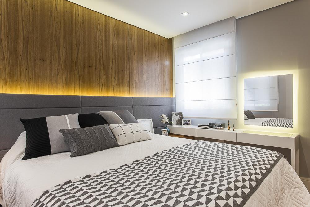 Quarto com parede de madeira e cama de casal. Roupa de cama geométrica preta e branca. Bancada aparador com espelho e penteadeira.