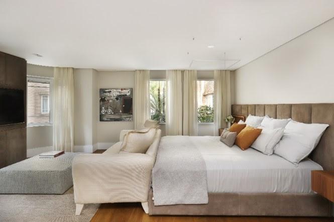 Quarto com paleta de cores clara. Cama de casal e sofá creme encostado no pé da cama. Televisão à frente no