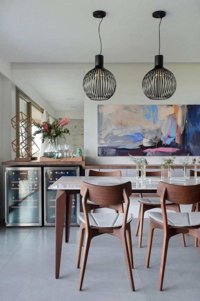 sala de jantar com mesa e cadeira de madeira e duas adegas