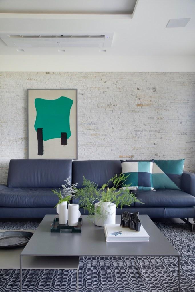 sala de estar com sofá azul e parede de tijolinhos