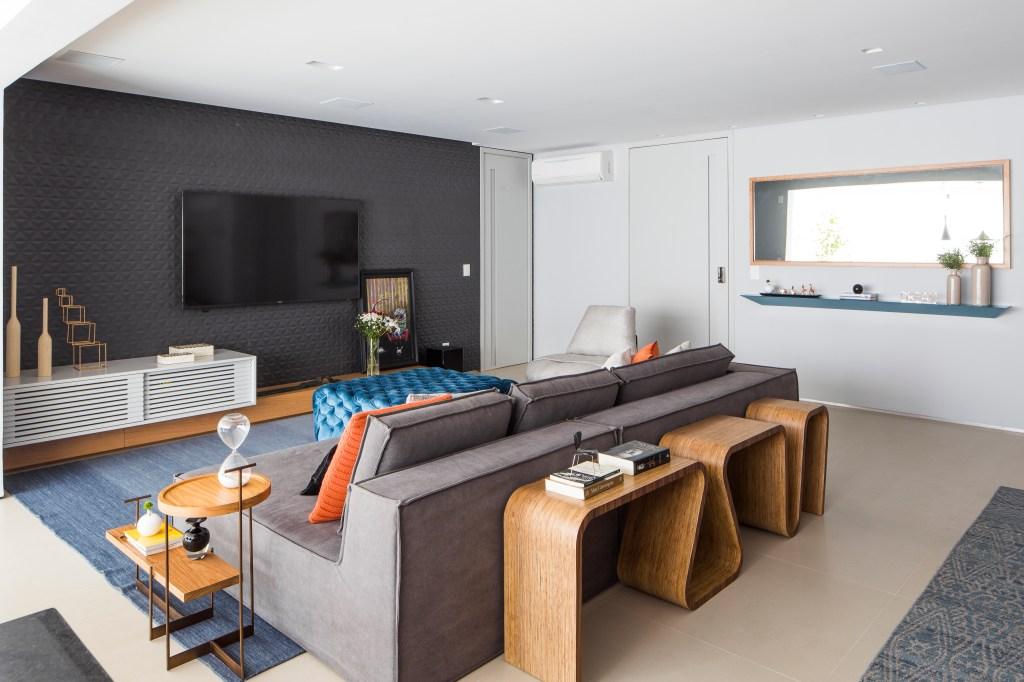 Sala de estar, com aparador de madeira atrás do sofá cinza. Na parede, um revestimento 3D cinza escuro
