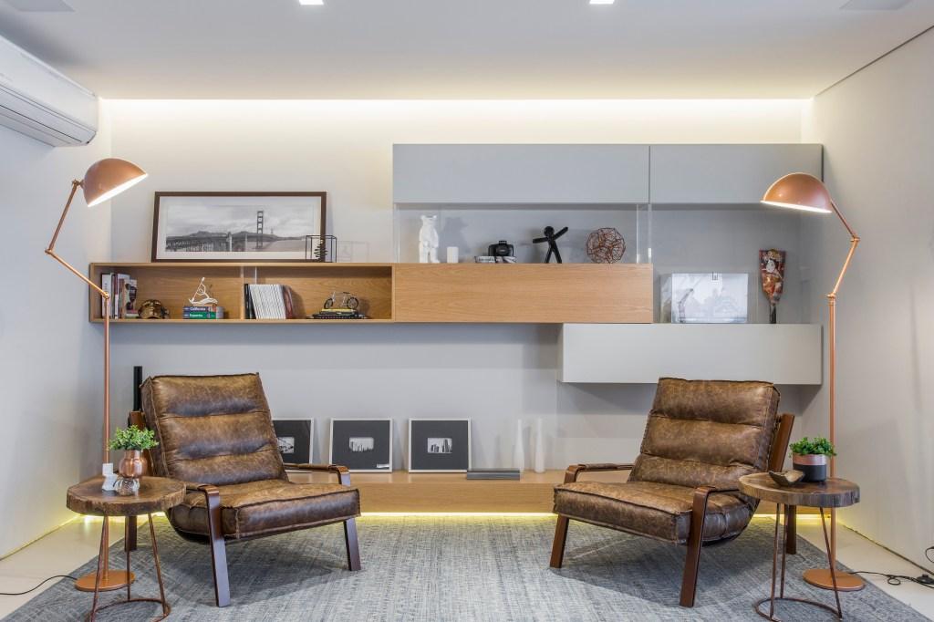 Sala de leitura com duas poltronas de couro, duas luminárias em rose gold; tapete cinza e nichos na parede nas cores de madeira natural e cinza