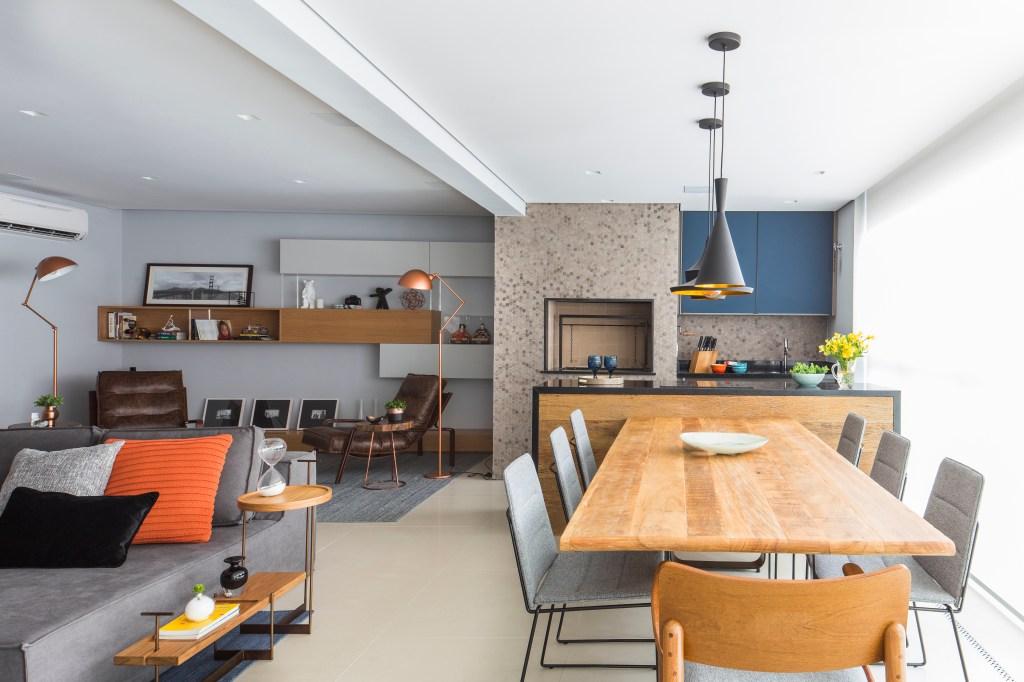 Sala e cozinha integradas, com mesa de 7 lugares à direita, com a cozinha ao fundo. Do lado esquerdo, uma parte do sofá cinza e ao fundo, uma sala de leitura, com duas poltronas de couro marrom, duas luminárias em rose gold