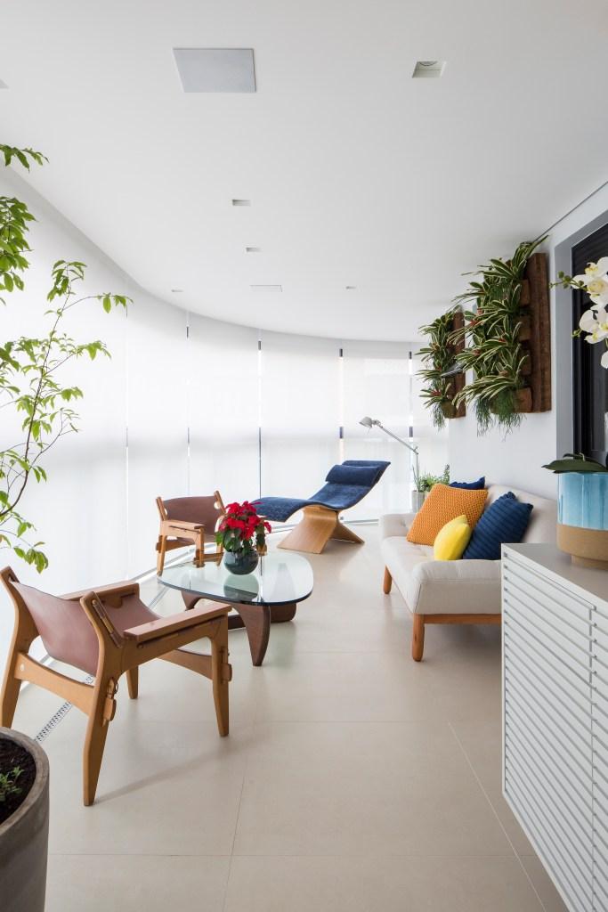 Varanda com cadeiras e sofá e piso de porcelanato branco. Nas paredes, plantas em vasos verticais.
