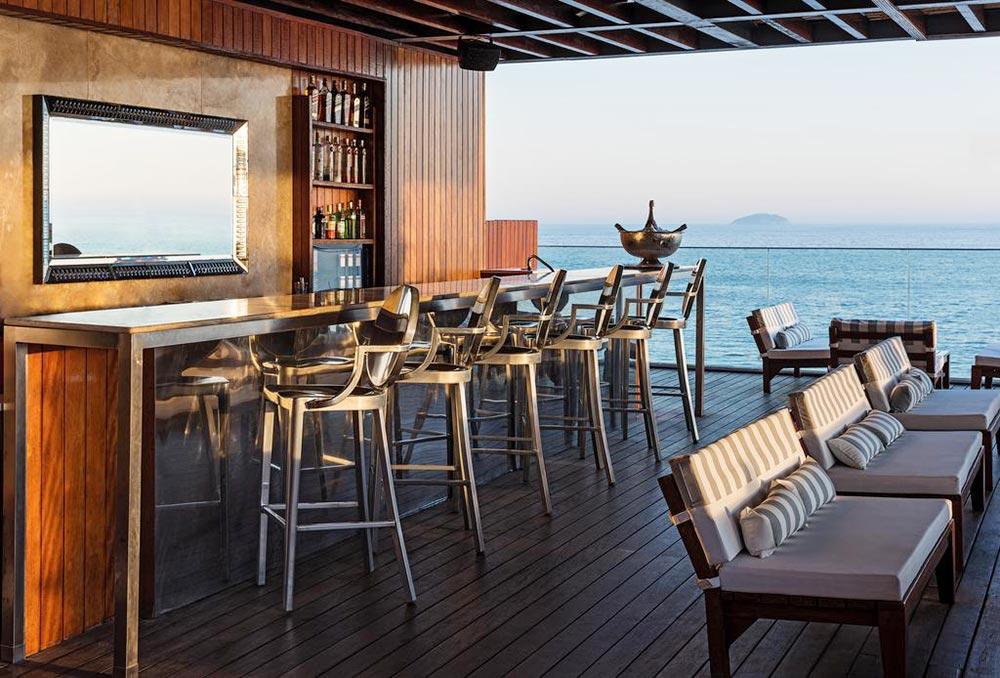Rooftop do Fasado, com deck, bar e cadeiras de madeira. Ao fundo, vista para o mar