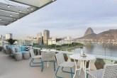 Cadeiras e mesas brancas no Rooftop do Yoo2, ao Fundo, a cidade do Rio De Janeiro, com o Pão de Açúcar e o mar.