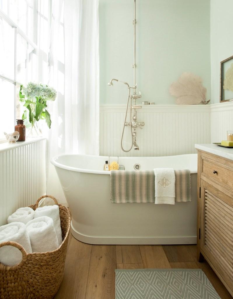 Banheiro com banheira em cores claras e piso de madeira