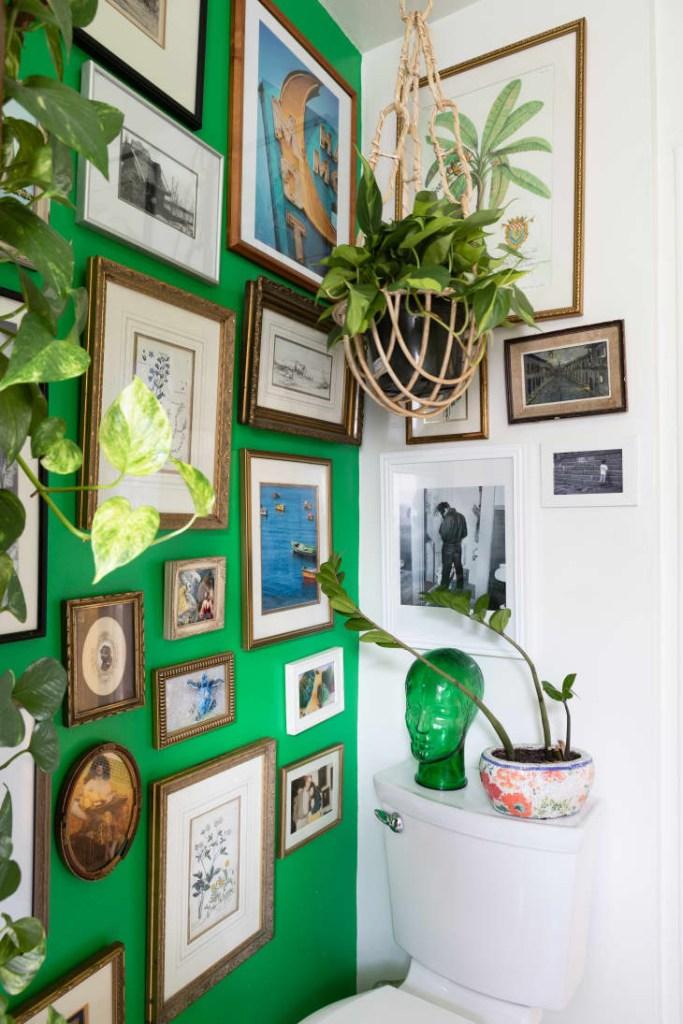 Banheiro com uma parede verde vibrante cheia de quadros, com fotos e pinturas em molduras de madeira de diversos tamanhos