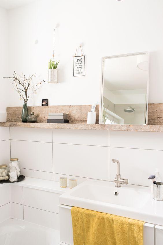 Banheiro com uma prateleira esguia de madeira acima da pia, com um espelho, planta e produtos de banheiro