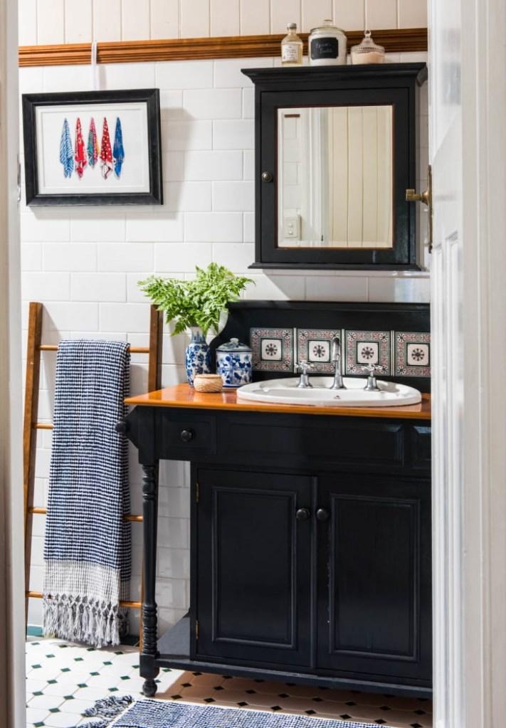 Banheiro com armário preto, com uma escada sendo usada para pendurar a toalha
