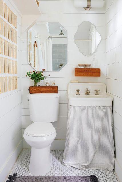Banheiro branco, com peças na mesma cor e parede com dois espelho lado a lado de tamanho e formato diferentes