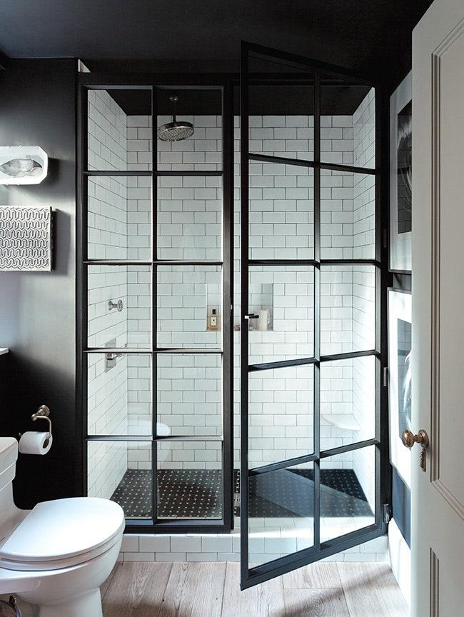 Banheiro preto e branco com box de vidro e estrutura quadrilculada preta