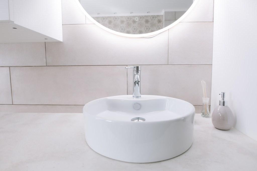 Pia do banheiro branca com espelho arredondado acima com uma luz na parte traseira dele