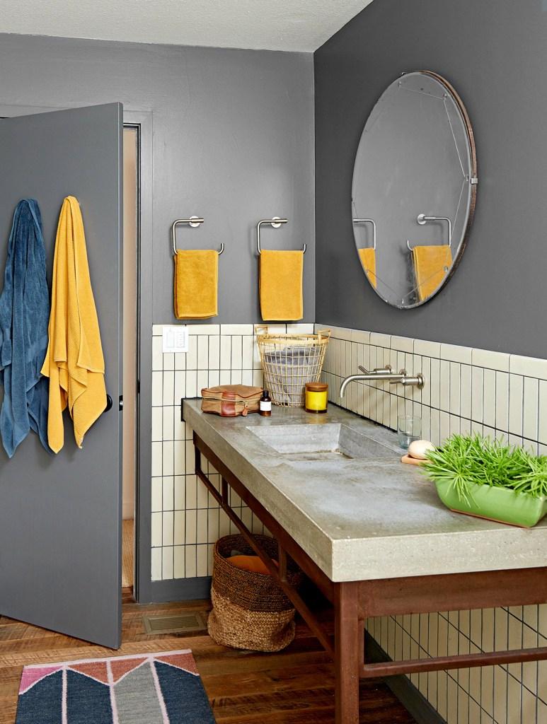 Banheiro cinza com toalhas amarelas e azuis