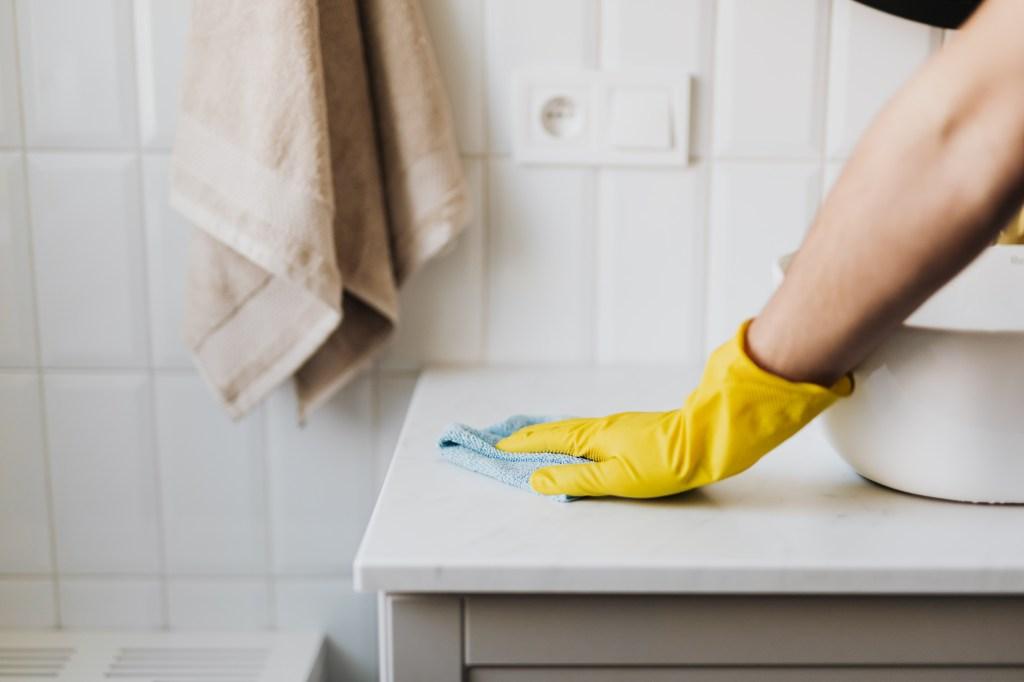 Mão com luva amarela limpando bancada de pia de banheiro