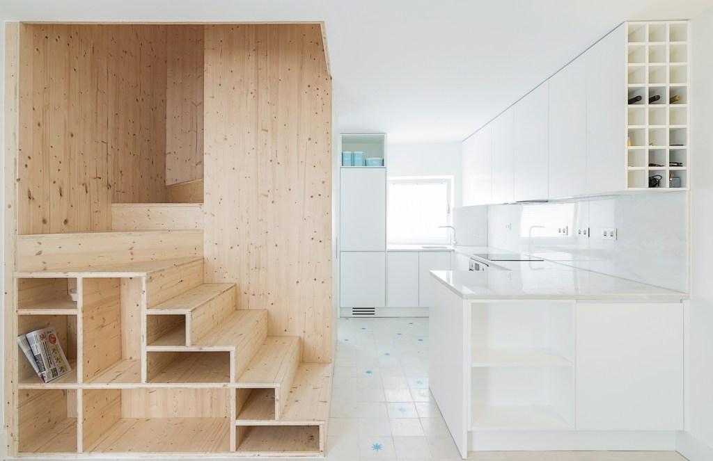 Escada de madeira com nichos abertos embaixo dela