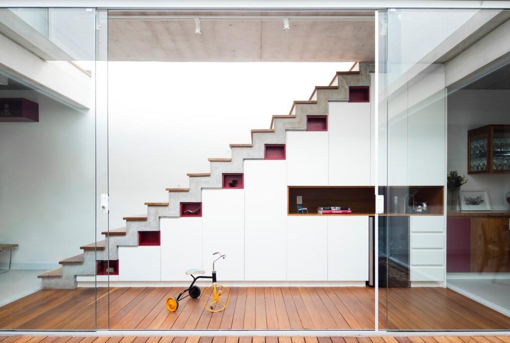 Escada branca com degraus em madeira, com a parte inferior dela servindo para expor pequenas esculturas
