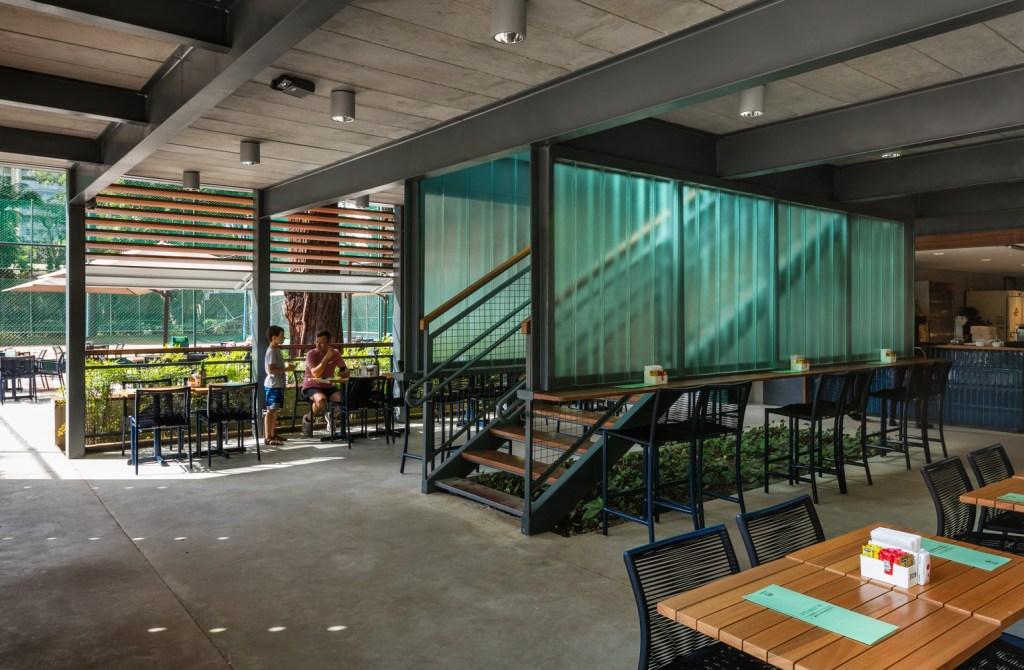 Escada de metal preto divindindo dois espaços em um restaurante