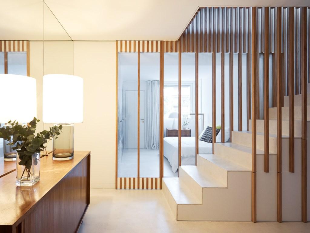 escada branca com estrutura de madeira divindindo dois cômodos