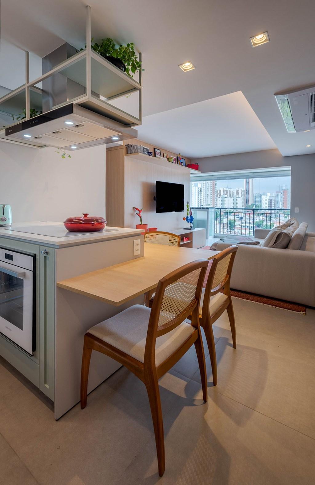 Living integrado com cozinha. Ilha de cozinha com cadeiras. Janela com vista da cidade ao fundo