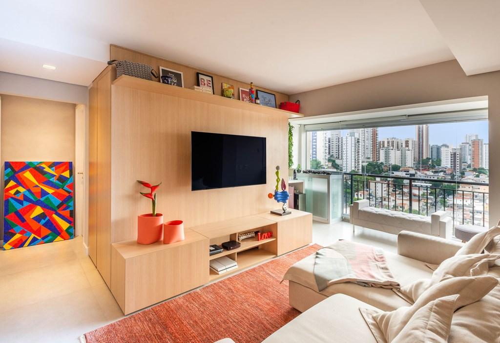 Living com piso branco e tapete vermelho. Móvel de madeira clara que funciona como hack e armário. Sofá branco. Quadro colorido na parede