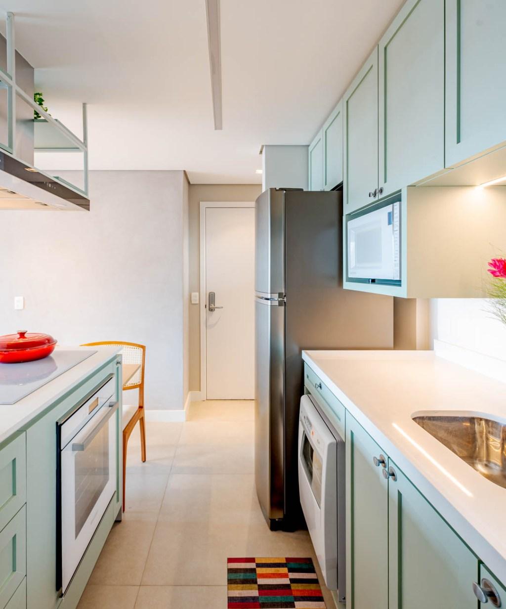 Cozinha com armários verde claros à direita e à esquerda, ilha com armários também verdes