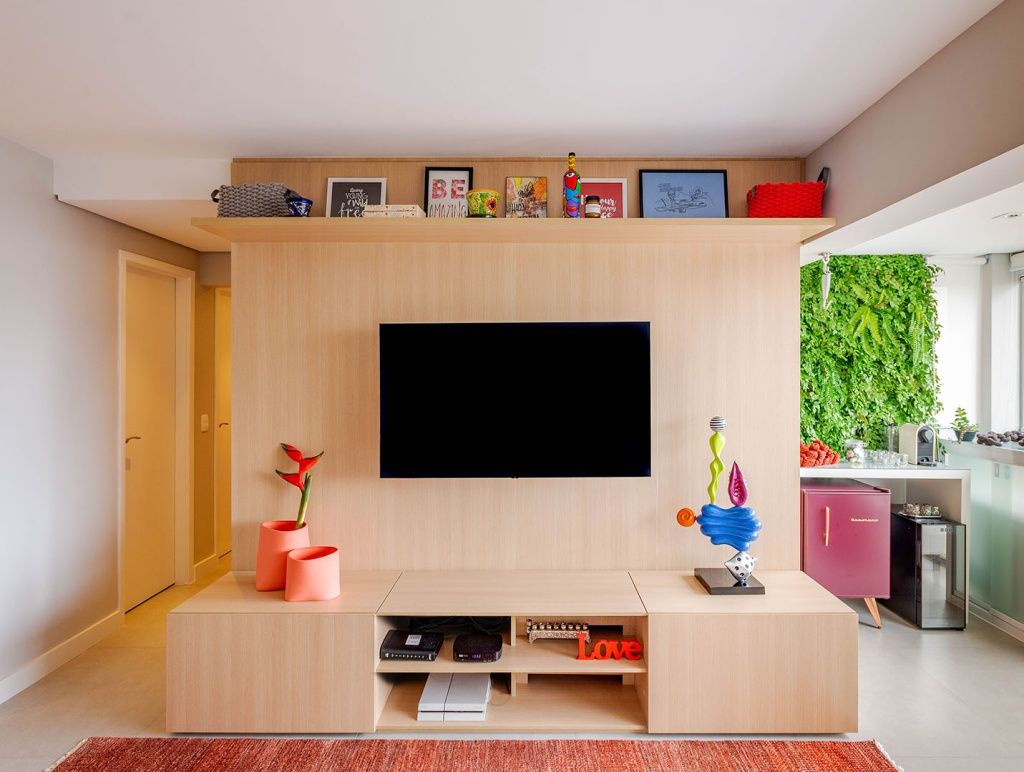 Móvel de madeira que serve como suporte da tv e armário. Prateleira no alto com porta retratos. Vaso laranja salmão. Varanda à direita