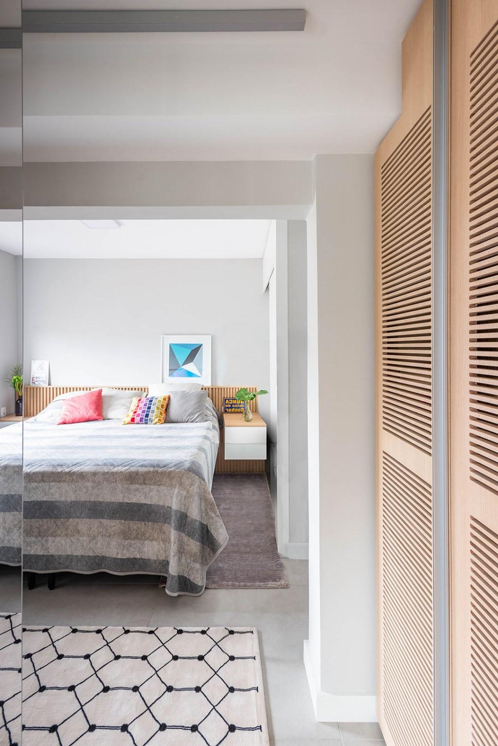 Quarto com cama de casal e fronha cinza listrada. Almofadas coloridas listradas. Armário de madeira