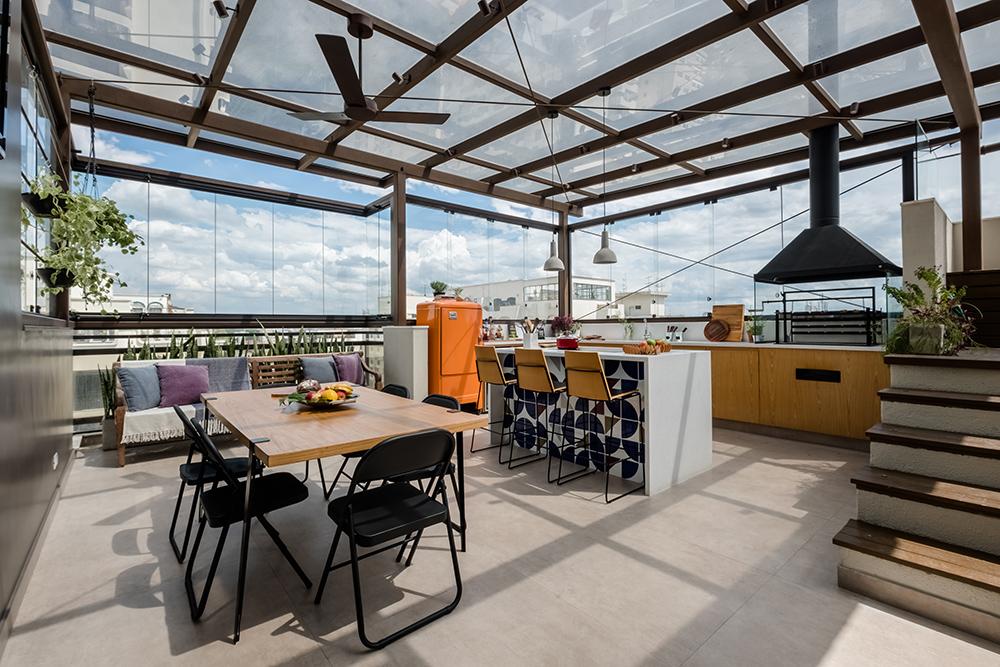 Cobertura com piso em concreto. Coberta com vidro. Mesa em madeira com cadeiras pretas. Ilha à direita com azulejos azuis. Cozinha com bancada e cooktop