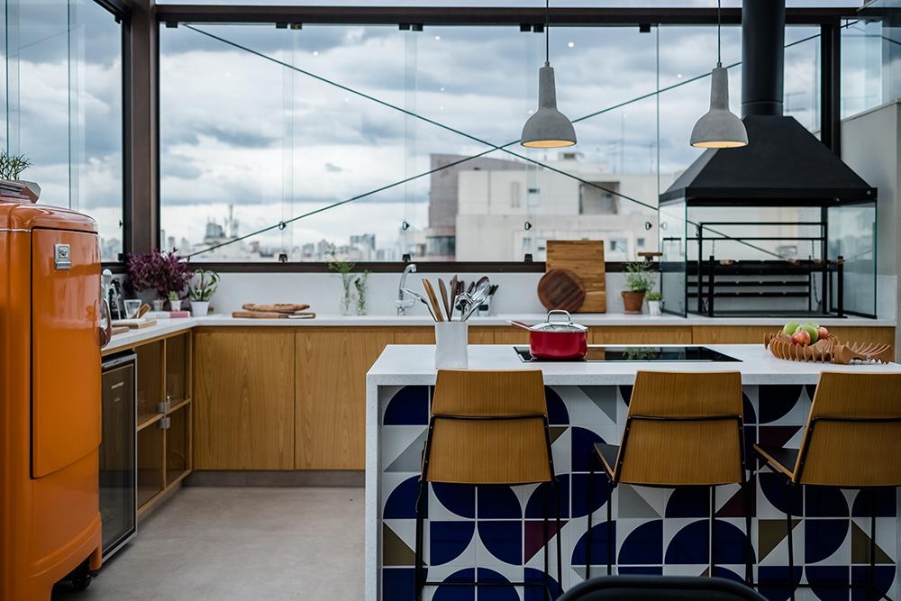 Cozinha com azulejos azuis e banco de madeira. Geladeira laranja à esquerda. Janelas grandes com vista para cidade