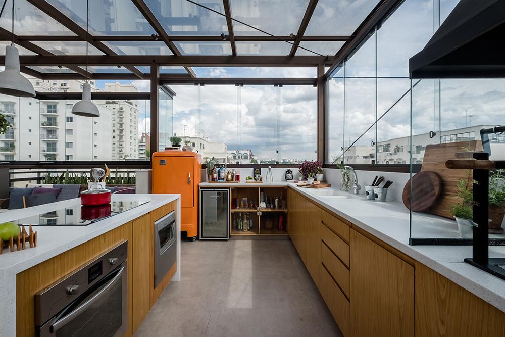 Cozinha com bancada em madeira revestida de branco. Geladeira laranja. Grandes janelas de vidro