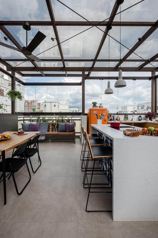 Cozinha com mesa em madeira à direita e bancada branca à esquerda. Ao fundo, grande banco de madeira e à direita geladeira laranja