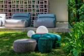 jardim com pufes verdes e cinzas e sofás cinzas ao fundo. Parede de cobogós rosa claro