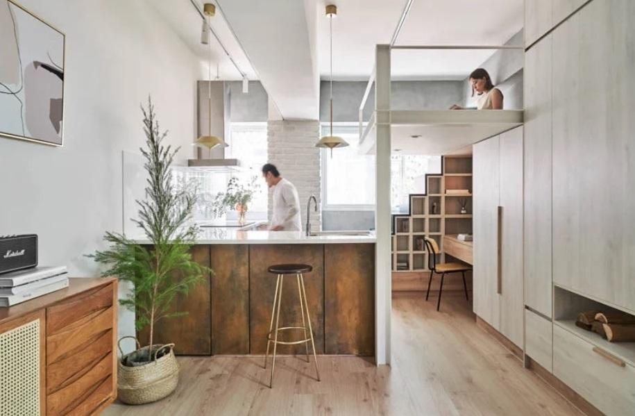 apartamento com piso em madeira, cozinha com bancada e um móvel em madeira com escada que leva a uma cama suspensa