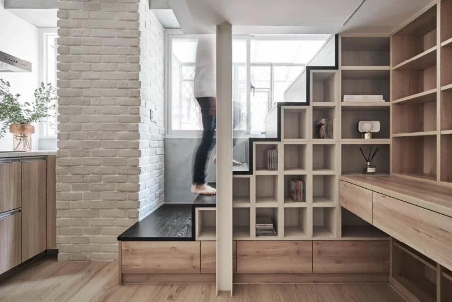 Móvel em marcenaria que forma a escada que leva à cama. No corte transversal da escada, nichos com livros