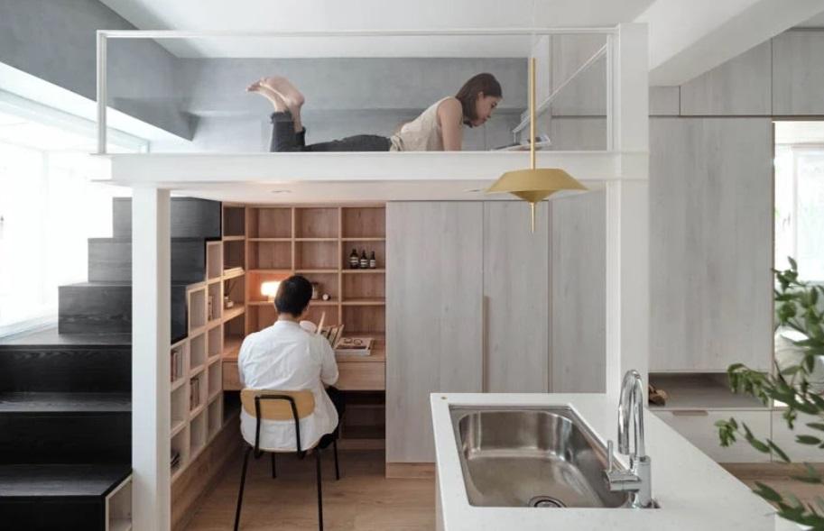 Homem trabalhando na parte de baixo do móvel em madeira. Mulher deitada na parte de cima