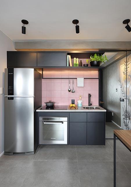 Cozinha com chão de cimento queimado, armários pretos e ladrilhos rosa