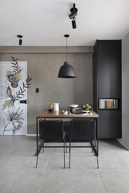 Cozinha com piso e parede de cimento queimado, com uma mesa de madeira e cadeiras pretas, com um desenho com uma rosto de uma mulher e flores na porta branca à esquerda